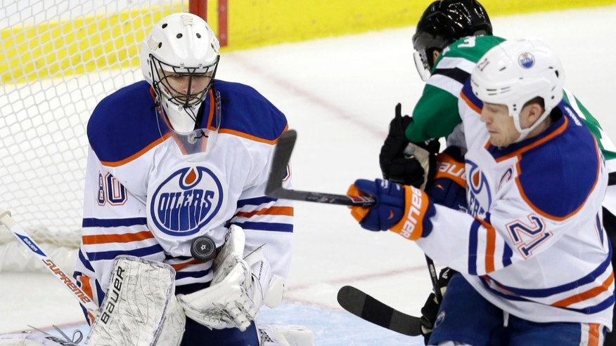 Edmonton Oilers goalie Ilya Bryzgalov (80) of Russia makes a stop as teammate Andrew Ference (21) ties up Dallas Stars left wing Ray Whitney during the first period of an NHL hockey game Sunday, Dec. 1, 2013, in Dallas.  (AP Photo/LM Otero)