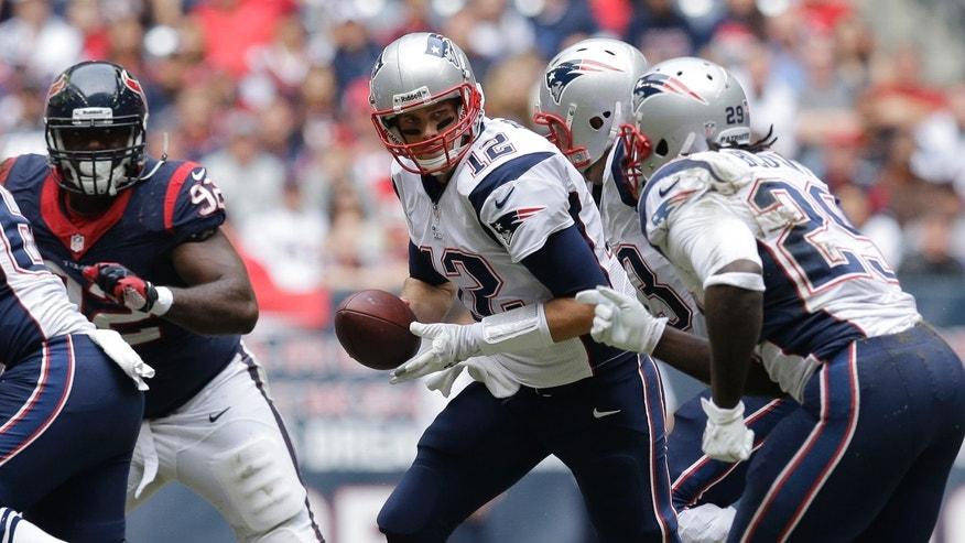 New England Patriots' Tom Brady (12) looks to hand off during the second quarter of an NFL football game against the Houston Texans, Sunday, Dec. 1, 2013, in Houston. (AP Photo/Patric Schneider)