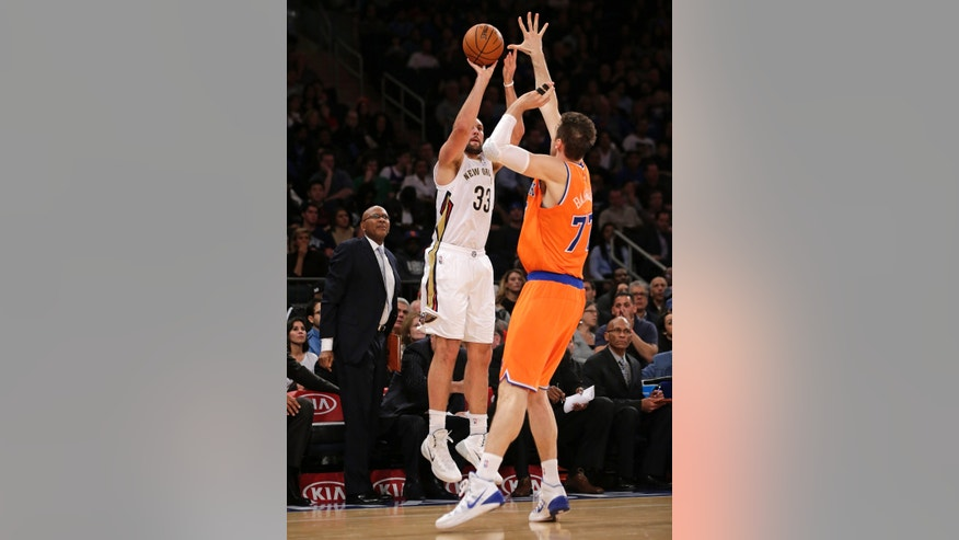 New Orleans Pelicans forward Ryan Anderson (33) shoots a three pointer as New York Knicks forward Andrea Bargnani (77) of Italy defends in the first half of their NBA basketball game at Madison Square Garden in New York, Sunday, Dec. 1, 2013.  (AP Photo/Kathy Willens)
