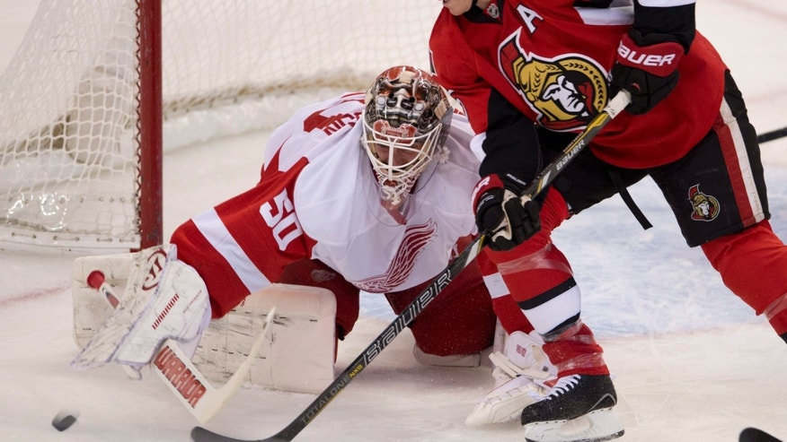 Ottawa Senators right wing Chris Neil (25) pressures Detroit Red Wings goalie Jonas Gustavsson for control of the puck during first period NHL action Sunday Dec. 1, 2013, in Ottawa, Ont.  (AP Photo/The Canadian Press, Adrian Wylde)