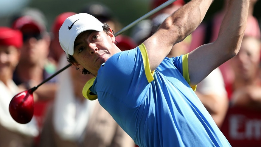 Rory McIlroy, left, of Northern Ireland watches his tee shot during his third round of the Australian Open Golf Tournament in Sydney, Australia, Saturday, Nov. 30, 2013.(AP Photo/Rob Griffith)