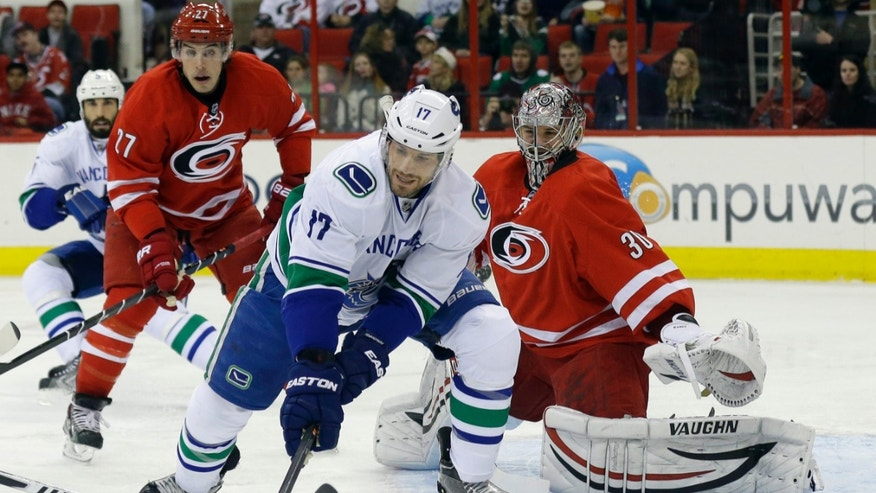 Carolina Hurricanes goalie Cam Ward (30) and Justin Faulk (27) defend as Vancouver Canucks' Ryan Kesler (17) tries to score during the first period of an NHL hockey game in Raleigh, N.C., Sunday, Dec. 1, 2013. (AP Photo/Gerry Broome)