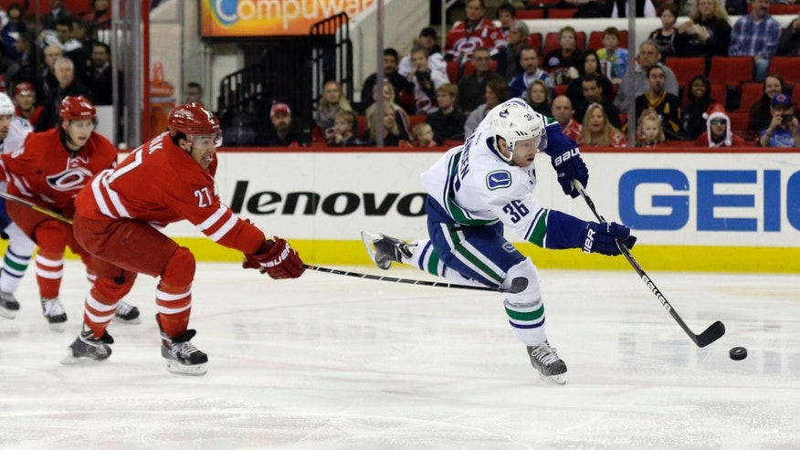 Carolina Hurricanes' Justin Faulk (27) defends as Vancouver Canucks' Jannik Hansen (36), of Denmark, shoots during the first period of an NHL hockey game in Raleigh, N.C., Sunday, Dec. 1, 2013. (AP Photo/Gerry Broome)