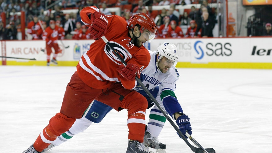Carolina Hurricanes' Tuomo Ruutu (15), of Finland, and Vancouver Canucks' Chris Tanev (8) chase the puck during the second period of an NHL hockey game in Raleigh, N.C., Sunday, Dec. 1, 2013. (AP Photo/Gerry Broome)