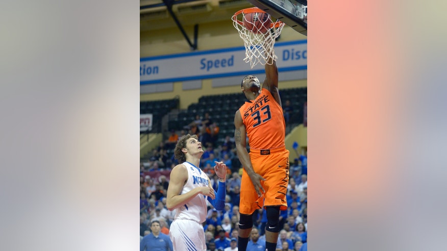 Oklahoma State guard Marcus Smart (33) dunks the ball in front of Memphis forward Austin Nichols, left, during the first half of an NCAA college basketball game at the Old Spice Classic tournament in Kissimmee, Fla., Sunday, Dec. 1, 2013.(AP Photo/Phelan M. Ebenhack)
