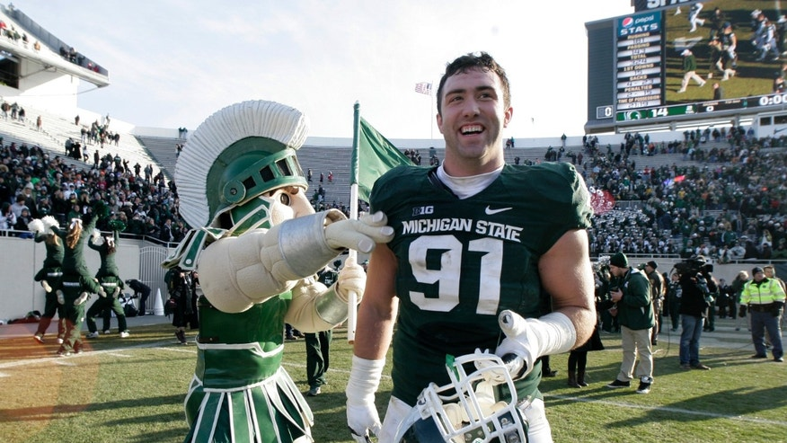 Michigan State's Tyler Hoover (91) celebrates with Sparty the mascot following a 14-3 win over Minnesota in an NCAA college football game, Saturday, Nov. 30, 2013, in East Lansing, Mich. (AP Photo/Al Goldis)