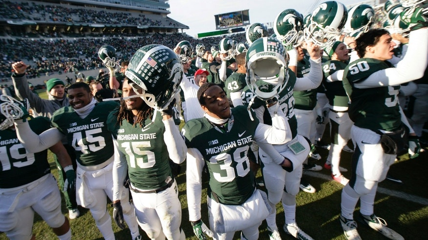 Michigan State players celebrate following their 14-3 win over Minnesota in an NCAA college football game, Saturday, Nov. 30, 2013, in East Lansing, Mich. (AP Photo/Al Goldis)