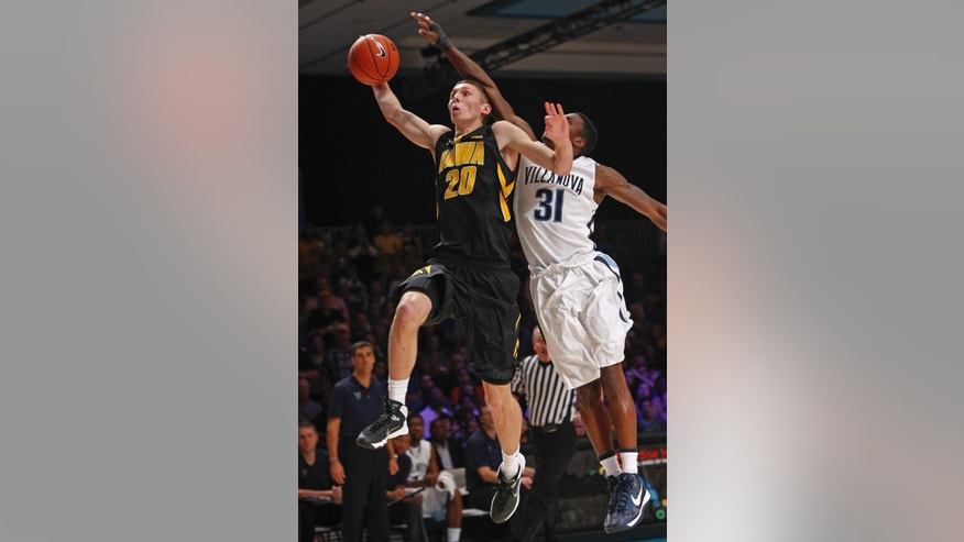 Iowa's Jarrod Uthoff, left, drives to the basket as Villanova's Dylan Ennis defends during the first half of an NCAA college basketball game in Paradise Island, Bahamas, Saturday, Nov. 30, 2013. (AP Photo/Bahamas Visual Services, Tim Aylen)