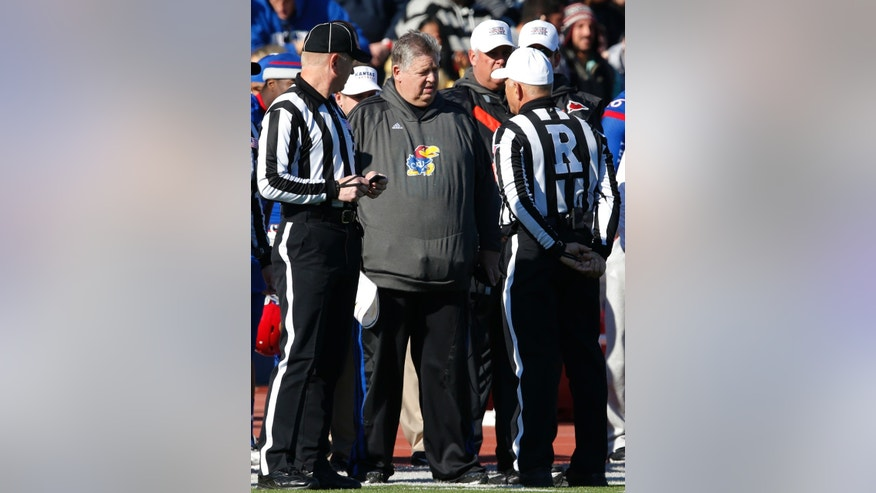 Kansas head coach Charlie Weis, center, talks with referee Cooper Castleberry, right, during the first half of an NCAA college football game against Kansas State in Lawrence, Kan., Saturday, Nov. 30, 2013. (AP Photo/Orlin Wagner)