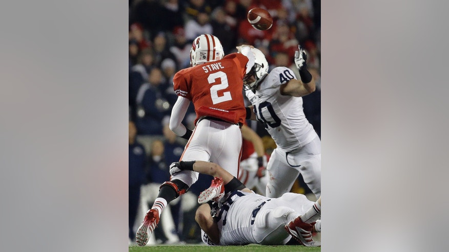 Wisconsin's Joel Stave (2) throws as he is hit by Penn State's Anthony Zettel during the second half of an NCAA college football game on Saturday, Nov. 30, 2013, in Madison, Wis. Penn State won 31-24. (AP Photo/Morry Gash)