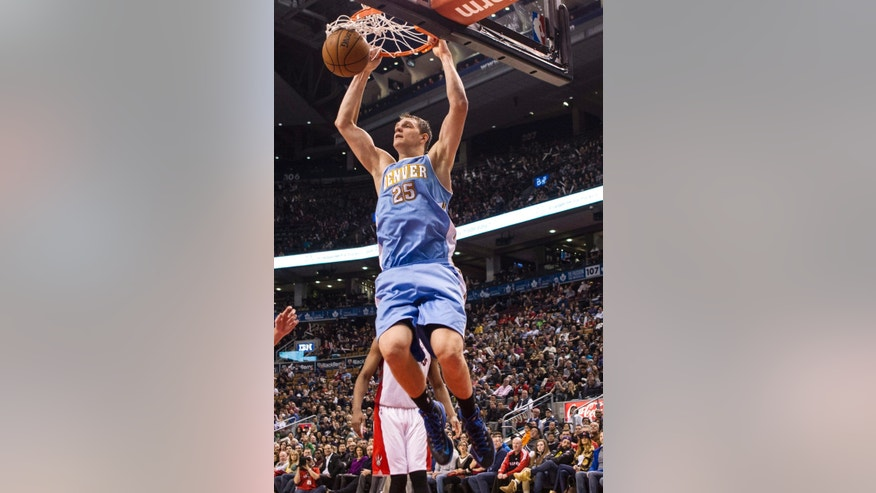 Denver Nuggets' Timofey Mozgov hangs from the hoop after scoring against the Toronto Raptors' during the second half of an NBA basketball game on Sunday, Dec. 1, 2013, in Toronto. (AP Photo/The Canadian Press, Chris Young)