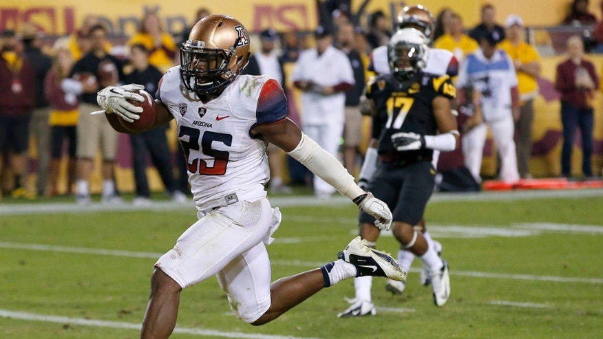 Arizona's Ka'Deem Carey (25) scores a touchdown as Arizona State's Lloyd Carrington (17) trails during the second half of an NCAA college football game Saturday, Nov. 30, 2013, in Tempe, Ariz.  Arizona State defeated Arizona 58-21. (AP Photo/Ross D. Franklin)