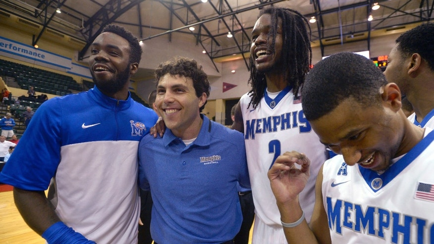Memphis head coach Josh Pastner, second from left, celebrates with players Damien Wilson, left, Shaq Goodwin (2) and Trey Draper (32) after their 73-68 victory over Oklahoma State in an NCAA college basketball game to win the Old Spice Classic tournament in Kissimmee, Fla., Sunday, Dec. 1, 2013.(AP Photo/Phelan M. Ebenhack)