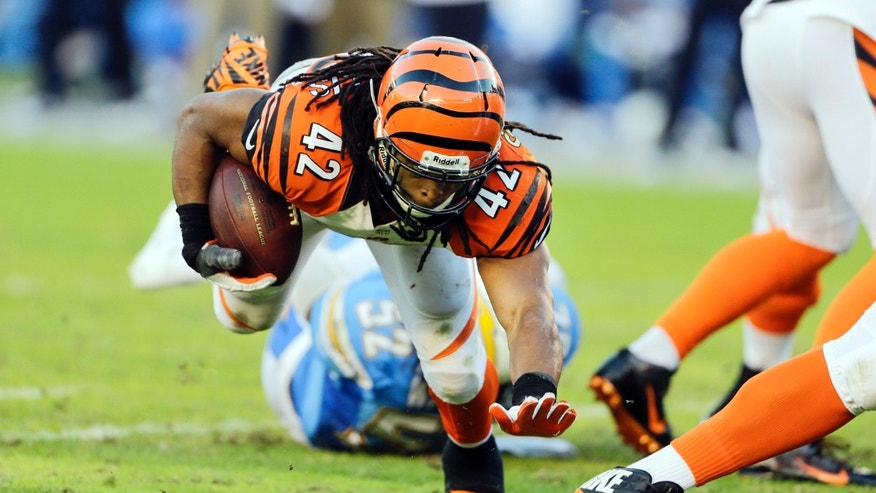 Cincinnati Bengals running back BenJarvus Green-Ellis keeps on his feet as he rushes against the San Diego Chargers during the second half of an NFL football game Sunday, Dec. 1, 2013, in San Diego. (AP Photo/Lenny Ignelzi)