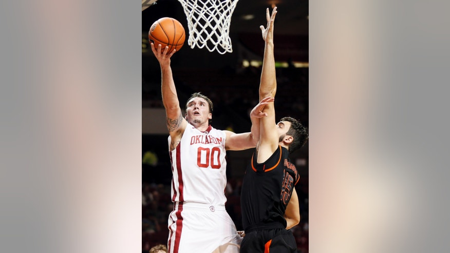 Oklahoma's Ryan Spangler (00) takes the ball to the hoop against Mercer's Monty Brown during an NCAA college basketball game in Norman, Okla., Monday, Dec. 2, 2013. (AP Photo/The Oklahoman, Nate Billings)