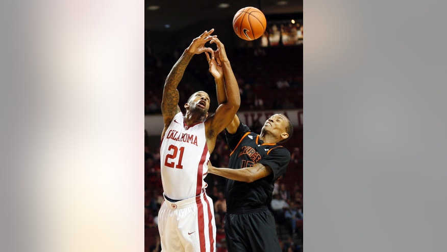 Oklahoma's Cameron Clark (21) and Mercer's Anthony White Jr. (15) chase a loose ball during an NCAA college basketball game in Norman, Okla., Monday, Dec. 2, 2013. (AP Photo/The Oklahoman, Nate Billings)