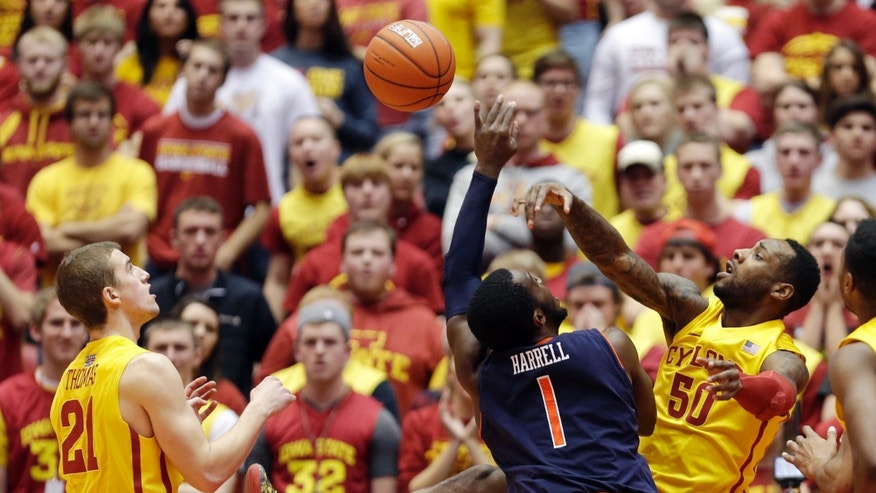 Auburn guard KT Harrell (1) drives to the basket between Iowa State guard Matt Thomas, left, and guard DeAndre Kane, right, during the first half of an NCAA college basketball game, Monday, Dec. 2, 2013, in Ames, Iowa. (AP Photo/Charlie Neibergall)