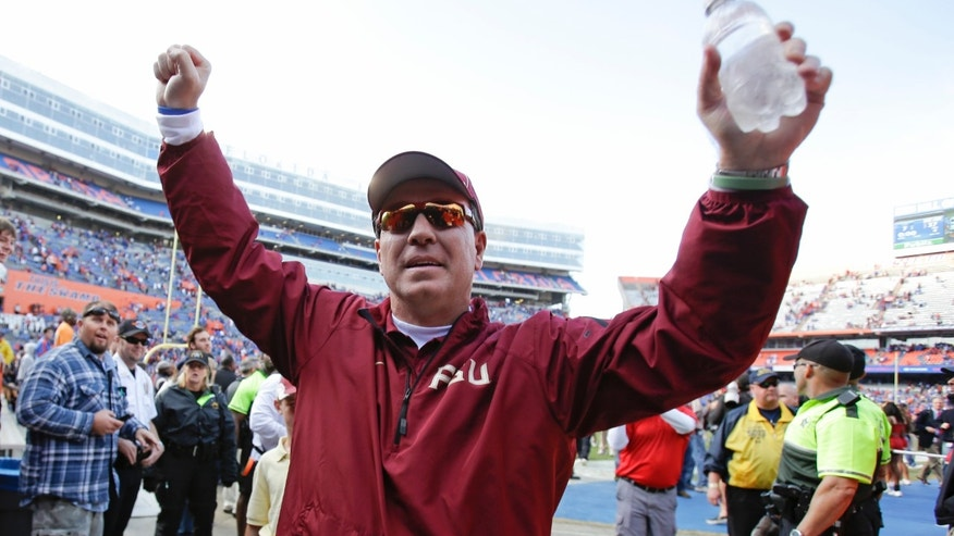 Florida State head coach Jimbo Fisher raises his arm to fans as he comes off the field after defeating Florida 37-7 in an NCAA college football game in Gainesville, Fla., Saturday, Nov. 30, 2013. (AP Photo/John Raoux)