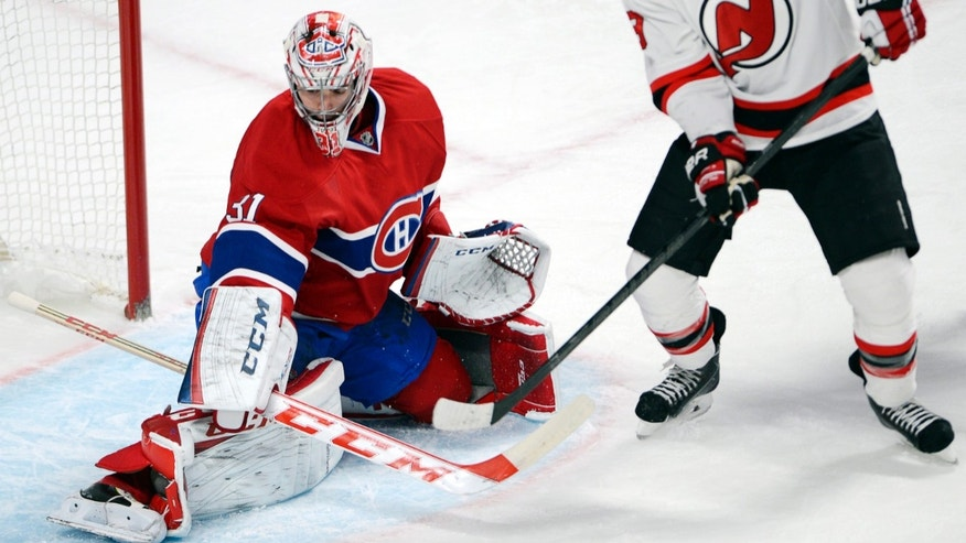Montreal Canadiens goalie Carey Price, left, stops New Jersey Devils center Travis Zajac during the second period of an NHL hockey game in Montreal on Monday, Dec. 2, 2013. (AP Photo/The Canadian Press, Ryan Remiorz)