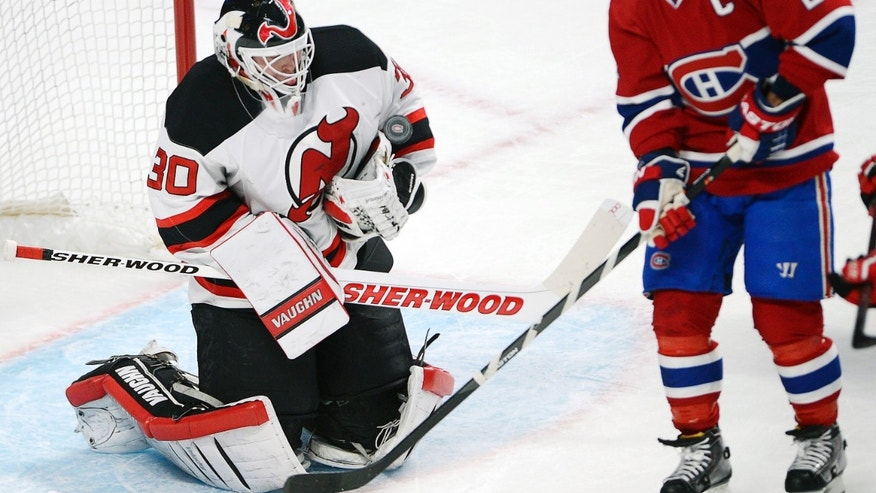 New Jersey Devils goalie Martin Brodeur (30) stops Montreal Canadiens right wing Brian Gionta during the first period of an NHL hockey game in Montreal on Monday, Dec. 2, 2013. (AP Photo/The Canadian Press, Ryan Remiorz)