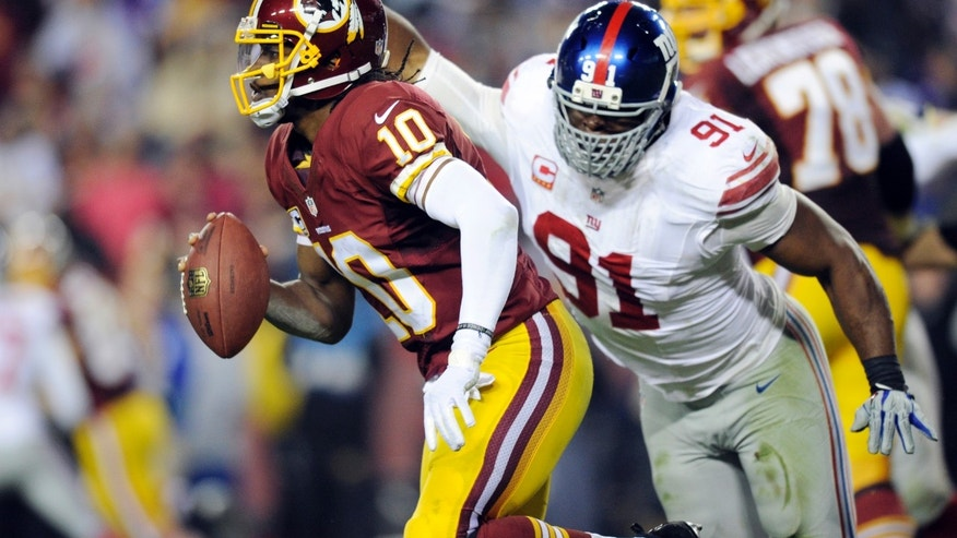 Washington Redskins quarterback Robert Griffin III (10) is pressured by New York Giants defensive end Justin Tuck (91) during the second half of an NFL football game Sunday, Dec. 1, 2013, in Landover, Md. The Giants won 24-17. (AP Photo/Nick Wass)