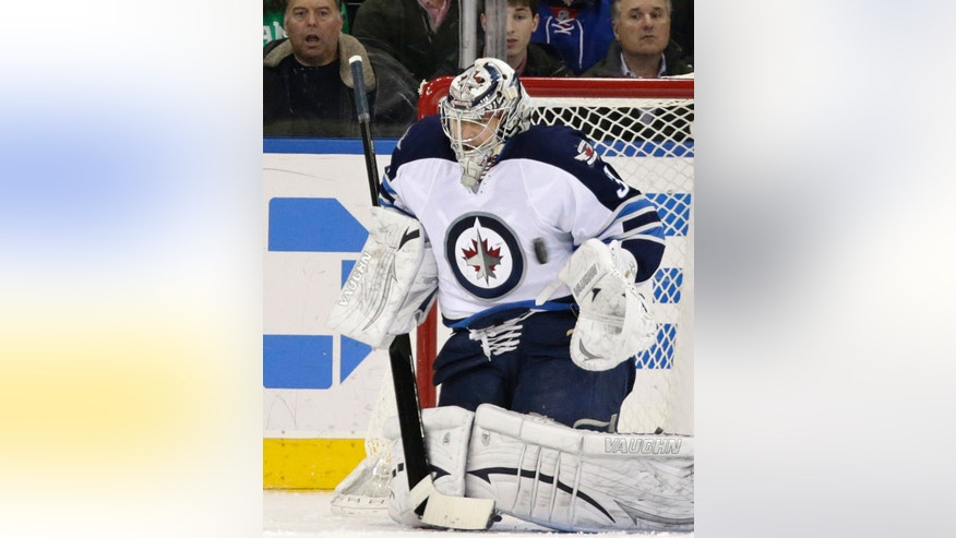 Winnipeg Jets goalie Ondrej Pavelec (31) of the Czech Republic makes a save in the first period of their NHL hockey game against the New York Rangers at Madison Square Garden in New York, Monday, Dec. 2, 2013.  (AP Photo/Kathy Willens)