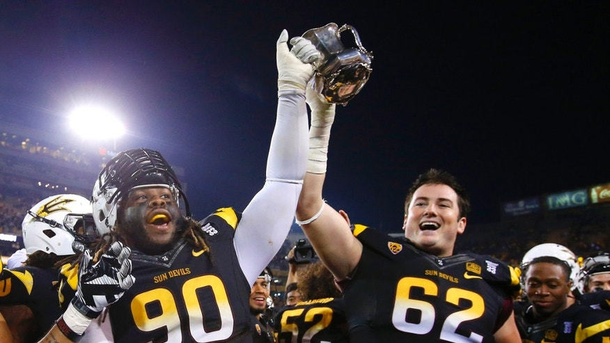 Arizona State's Will Sutton (90) and Evan Finkenberg (62) hold the Territorial Cup in celebration after an NCAA college football game against Arizona Saturday, Nov. 30, 2013, in Tempe, Ariz.  Arizona State defeated Arizona 58-21. (AP Photo/Ross D. Franklin)