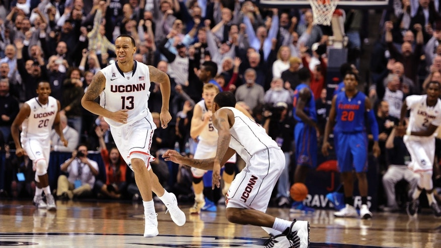 Connecticut's Shabazz Napier, left, and Ryan Boatright, right, react after Napier hits the game winning basket at the end an NCAA college basketball game against Florida, Monday, Dec. 2, 2013, in Storrs, Conn. Connecticut won 65-64. (AP Photo/Jessica Hill)
