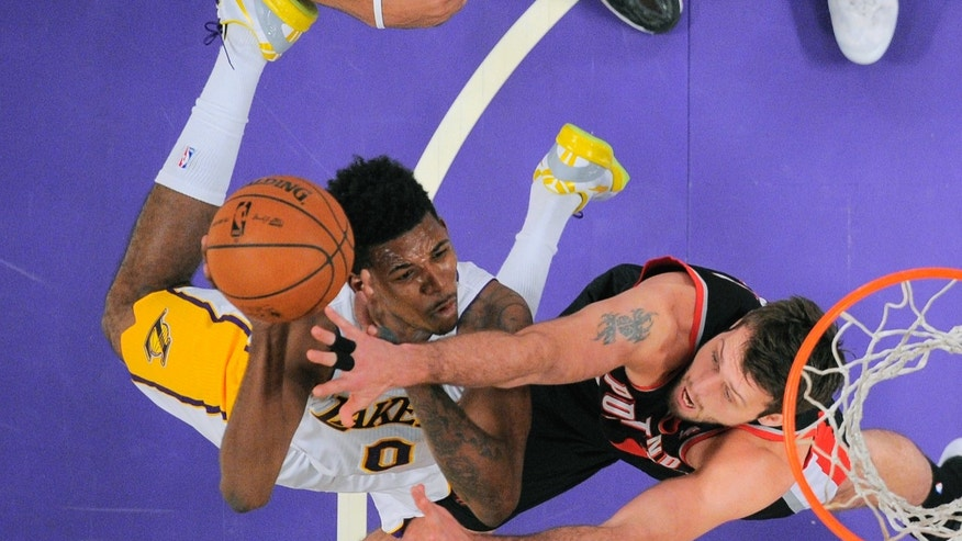 Los Angeles Lakers forward Nick Young, left, puts up a shot as Portland Trail Blazers center Joel Freeland, of England, defends during the first half of an NBA basketball game Sunday, Dec. 1, 2013, in Los Angeles. (AP Photo/Mark J. Terrill)