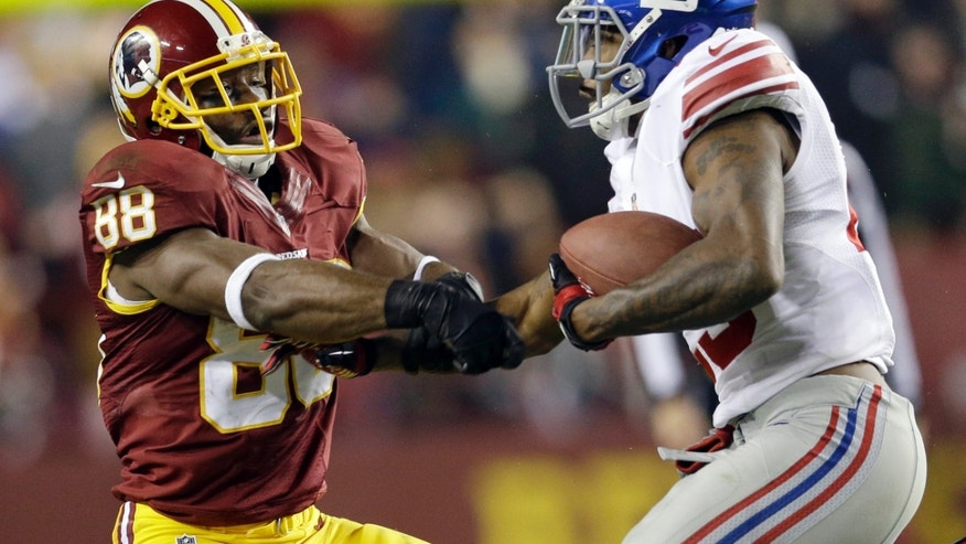 New York Giants free safety Will Hill, right, takes the football away from Washington Redskins wide receiver Pierre Garcon (88) during the second half of an NFL football game Sunday, Dec. 1, 2013, in Landover, Md. The Giants won 24-17. (AP Photo/Patrick Semansky)