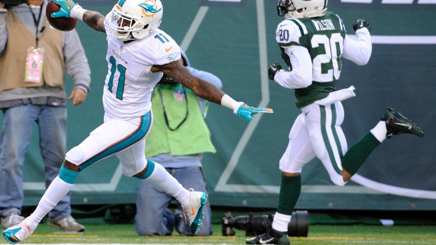 Miami Dolphins wide receiver Mike Wallace (11) celebrates after scoring a touchdown as New York Jets cornerback Kyle Wilson (20) runs behind him during the second half of an NFL football game, Sunday, Dec. 1, 2013, in East Rutherford, N.J. (AP Photo/Bill Kostroun)