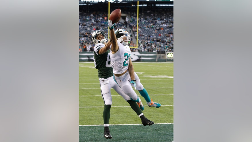 Miami Dolphins cornerback Brent Grimes (21) breaks up a pass intended for New York Jets wide receiver David Nelson (86) during the second half of an NFL football game on Sunday, Dec. 1, 2013, in East Rutherford, N.J. (AP Photo/Seth Wenig)