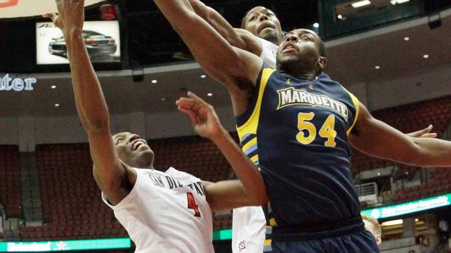 Marquette forward Davante Gardner (54) shoots as San Diego State guard Dakarai Allen (4) and forward Josh Davis defend in the first half of an NCAA college basketball game at the Wooden Legacy tournament in Anaheim, Calif., Sunday, Dec. 1, 2013. (AP Photo/Reed Saxon)