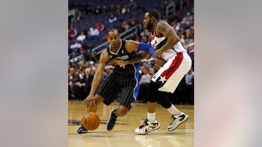 Orlando Magic shooting guard Arron Afflalo (4) drives past Washington Wizards forward Trevor Booker (35) in the first half of an NBA basketball game Monday, Dec. 2, 2013, in Washington. (AP Photo/Alex Brandon)