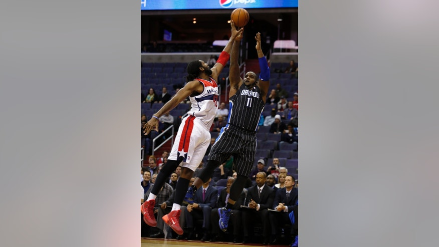 Washington Wizards forward Nene (42), from Brazil, blocks a shot by Orlando Magic forward Glen Davis (11) in the first half of an NBA basketball game Monday, Dec. 2, 2013, in Washington. (AP Photo/Alex Brandon)