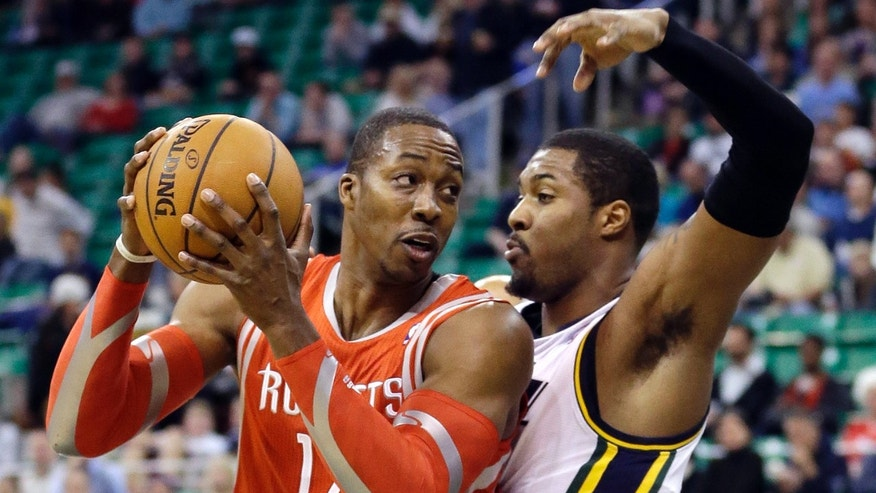 Utah Jazz's Derrick Favors, right, defends against Houston Rockets' Dwight Howard in the first quarter of an NBA basketball game Monday, Dec. 2, 2013, in Salt Lake City. (AP Photo/Rick Bowmer)