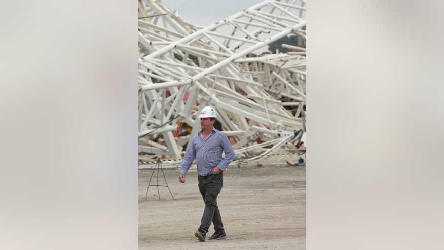 Former Corinthians president Andres Sanchez walks past the damage caused by the collapse at the Corinthians Arena stadium that will host the opening match of the World Cup, five days after an accident killed two workers, in Sao Paulo, Brazil, Monday, Dec. 2, 2013. Construction company Odebrecht had suspended work on the site after a crane collapsed on Wednesday, Nov. 27, as it was hoisting a 500-ton piece of roofing. (AP Photo/Andre Penner)