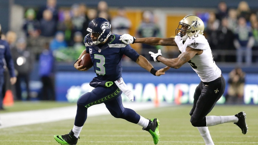 Seattle Seahawks quarterback Russell Wilson, left, pushes off New Orleans Saints cornerback Keenan Lewis, right, as Wilson keeps the ball in the first half of an NFL football game, Monday, Dec. 2, 2013, in Seattle. (AP Photo/Elaine Thompson)