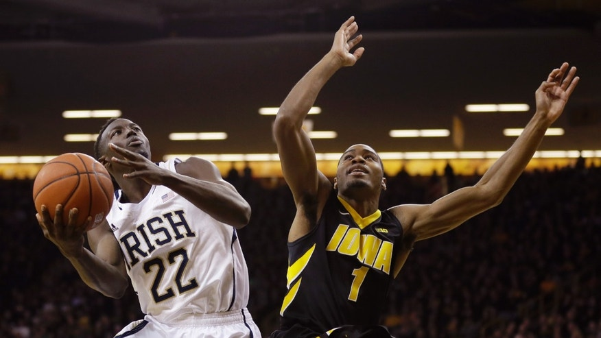Notre Dame guard Jerian Grant, left, drives to the basket past Iowa forward Melsahn Basabe during the first half of an NCAA college basketball game, Tuesday, Dec. 3, 2013, in Iowa City, Iowa. (AP Photo/Charlie Neibergall)