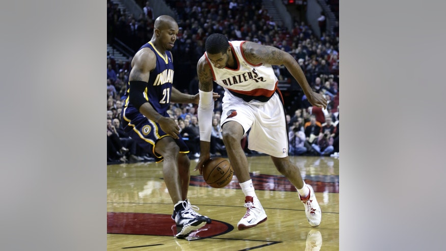Portland Trail Blazers forward LaMarcus Aldridge, right, loses his handle on the ball as he drives to the basket against Indiana Pacers forward David West during the first half of an NBA basketball game in Portland, Ore., Monday, Dec. 2, 2013. (AP Photo/Don Ryan)