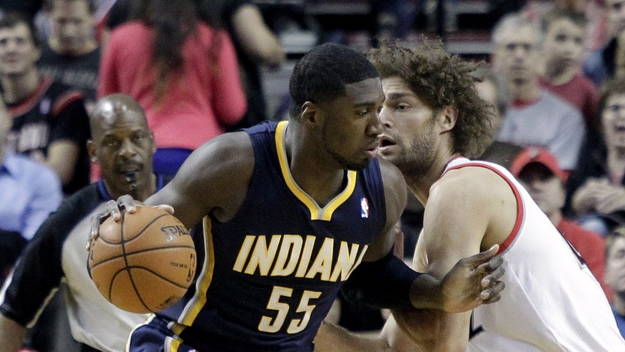 Indiana Pacers center Roy Hibbert, left, backs in on Portland Trail Blazers center Robin Lopez during the first half of an NBA basketball game in Portland, Ore., Monday, Dec. 2, 2013. (AP Photo/Don Ryan)