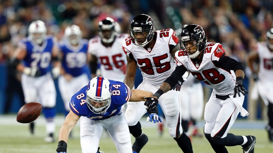 Buffalo Bills tight end Scott Chandler (84) fumbles the ball in front of Atlanta Falcons defenders William Moore (25) and Thomas DeCoud (28) during overtime in an NFL football game on Sunday, Dec. 1, 2013, in Toronto. Atlanta recovered on the play and won 34-31. (AP Photo/Gary Wiepert)