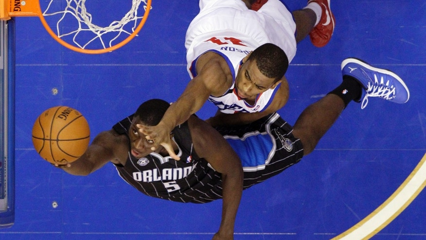 Orlando Magic's Victor Oladipo (5) goes up for a shot against Philadelphia 76ers' Hollis Thompson (31) during the first half of an NBA basketball game, Tuesday, Dec. 3, 2013, in Philadelphia. (AP Photo/Matt Slocum)