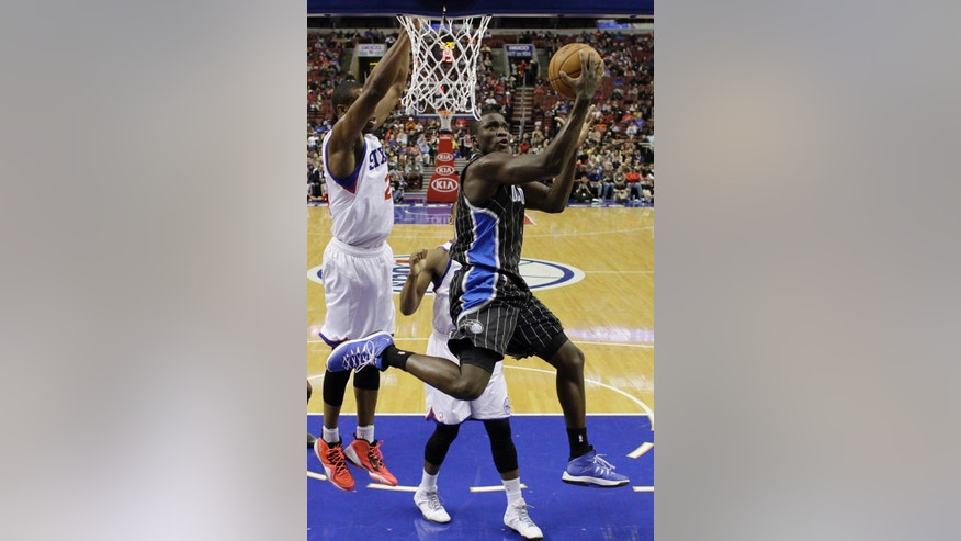 Orlando Magic's Victor Oladipo, right, goes up for a shot against Philadelphia 76ers' Thaddeus Young during the first half of an NBA basketball game, Tuesday, Dec. 3, 2013, in Philadelphia. (AP Photo/Matt Slocum)