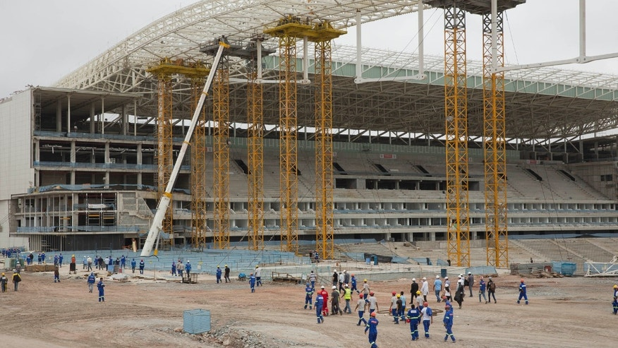 Construction workers return to the Arena Corinthians stadium that will host the opening match of the World Cup, five days after an accident killed two workers, in Sao Paulo, Brazil, Monday, Dec. 2, 2013. Construction company Odebrecht had suspended work on the site after a crane collapsed on Wednesday, Nov. 27, as it was hoisting a 500-ton piece of roofing. (AP Photo/Andre Penner)