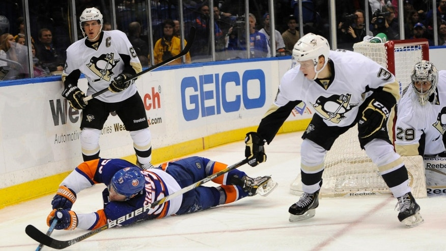 New York Islanders' Casey Cizikas (53) dives to the ice to keep the puck away from Pittsburgh Penguins' Olli Maatta (3) as Sidney Crosby (87) watches from behind in the second period of an NHL hockey game on Tuesday, Dec. 3, 2013, in Uniondale, N.Y. (AP Photo/Kathy Kmonicek)