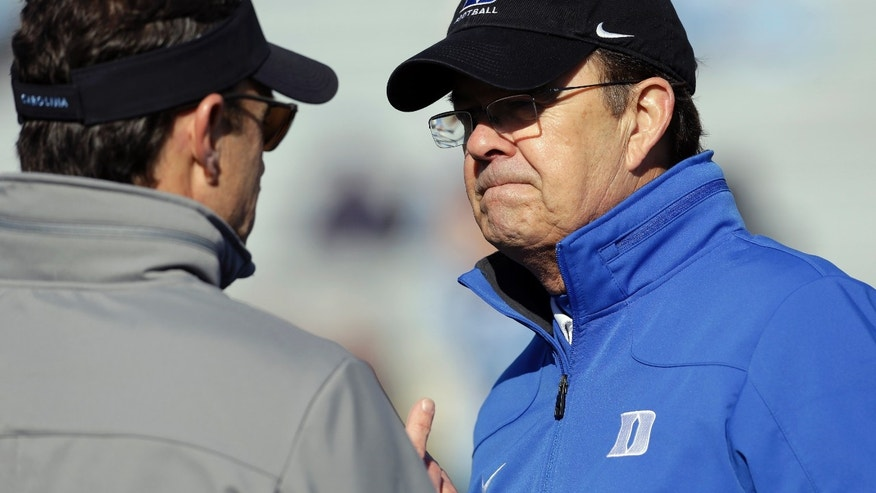 Duke coach David Cutcliffe, right, speaks with North Carolina coach Larry Fedora prior to an NCAA college football game in Chapel Hill, N.C., Saturday, Nov. 30, 2013. (AP Photo/Gerry Broome)