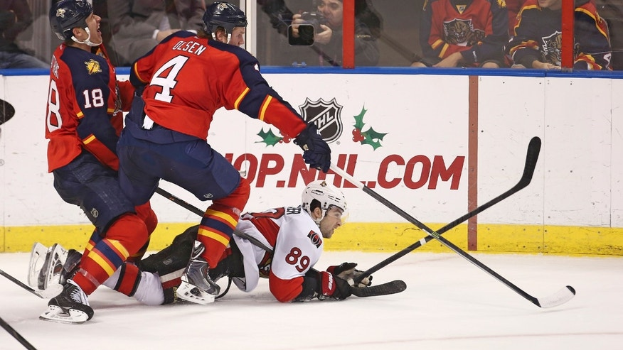 Florida Panthers players Dylan Olsen (4) and Shawn Matthias (18) battle Ottawa Senators' Cory Conacher (89) for the puck during the second period of a NHL hockey game in Sunrise, Fla., Tuesday, Dec. 3, 2013. (AP Photo/J Pat Carter)