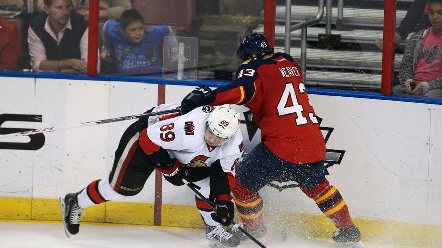 Ottawa Senators' Cory Conacher (89) and Florida Panghers' Mike Weaver (43) collide as they chase the puck during the third period of a NHL hockey game in Sunrise, Fla., Tuesday, Dec. 3, 2013. The Senators won 4-2. (AP Photo/J Pat Carter)