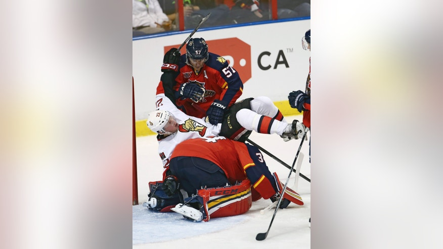 Florida Panthers' Marcel Goc (57) pulls Ottawa Senators' Erik Condra (22) off goalie Tim Thomas, after Condra fell on Thomas during the second period of a NHL hockey game in Sunrise, Fla., Tuesday, Dec. 3, 2013. (AP Photo/J Pat Carter)